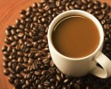 Cup of coffee and coffee beans on brown background.